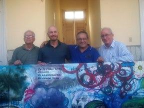 De izquierda a derecha: P. Catasús, Tomás Sánchez, Hno Manuel Pliego y P. José María Vigil, detrás del mural colectivo realizado por los artistas participantes en el taller