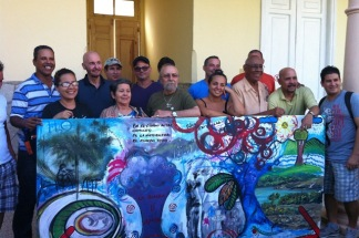 Artistas participantes en el taller posan detrás del mural colectivo realizado por ellos.