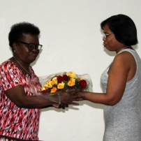 Belkis Guerrero (CCAM) otorga un ramo de flores a nombre del Centro Cultural